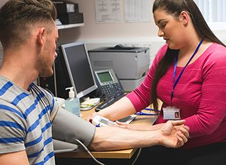 A nurse is taking a man's blood pressure