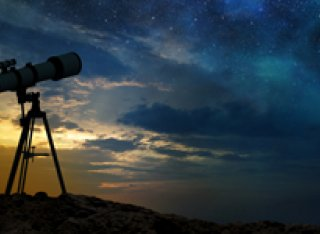 Telescope on hill at night with stars shining