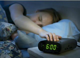 Sleeping person reaching to turn the alarm off