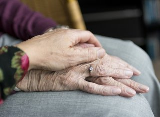 Carer holding hand of an elderly woman