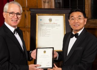 Professor Simon de Lusignan receives a framed certificate from Professor Max Lu