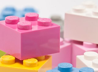 A close up of a pile of pink, blue, yellow and white Lego blocks