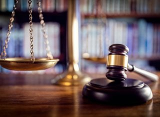 The image shows a gavel and scales of justice in a legal office
