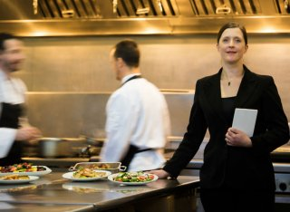 A restaurant manager stands in a busy hotel restaurant kitchen
