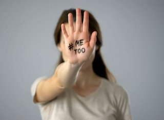 A lady holds her hand to the camera and it has 'Me Too' written on it