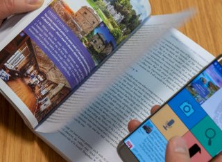 Somebody uses a mobile phone to interact with an augmented travel guide