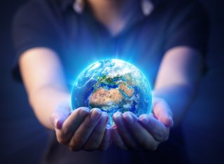 A person holds a shining globe in their hands