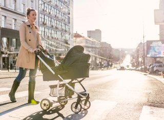 Mother pushing her baby in a pram across a road