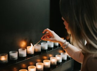 Woman lighting candle for Holocaust Memorial Day