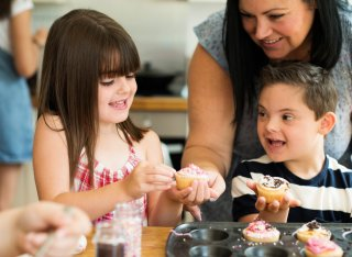 Children decorating cupcakes with their mum