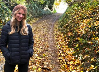 Emily Baynes standing on a country lane in autumn