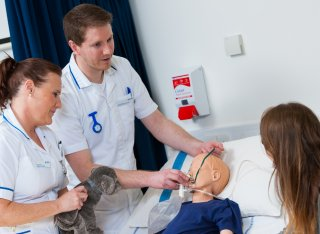 Two nursing students treating a child mannequin while talking to a parent