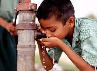 Boy drinking water from a pump