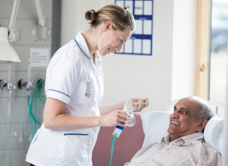 Student nurse putting breathing mask on elderly patient laying in a bed