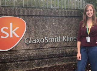 Biosciences student, Chloe Charlwood, standing in front of a GlaxoSmithKline (GSK) sign