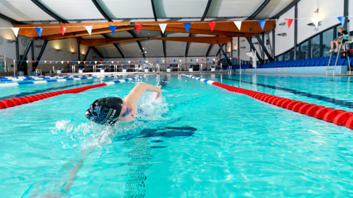 Male swimmer doing front crawl in the Olympic-sized pool at Surrey Sports Park