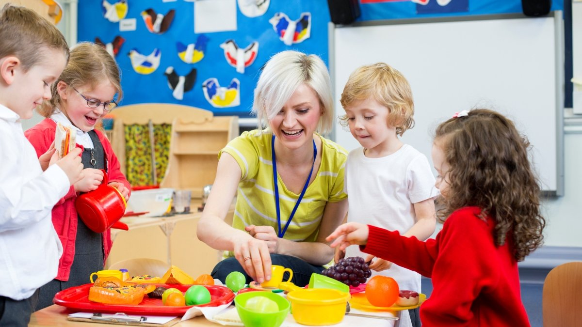 Children in a nursery with an adult teaching them