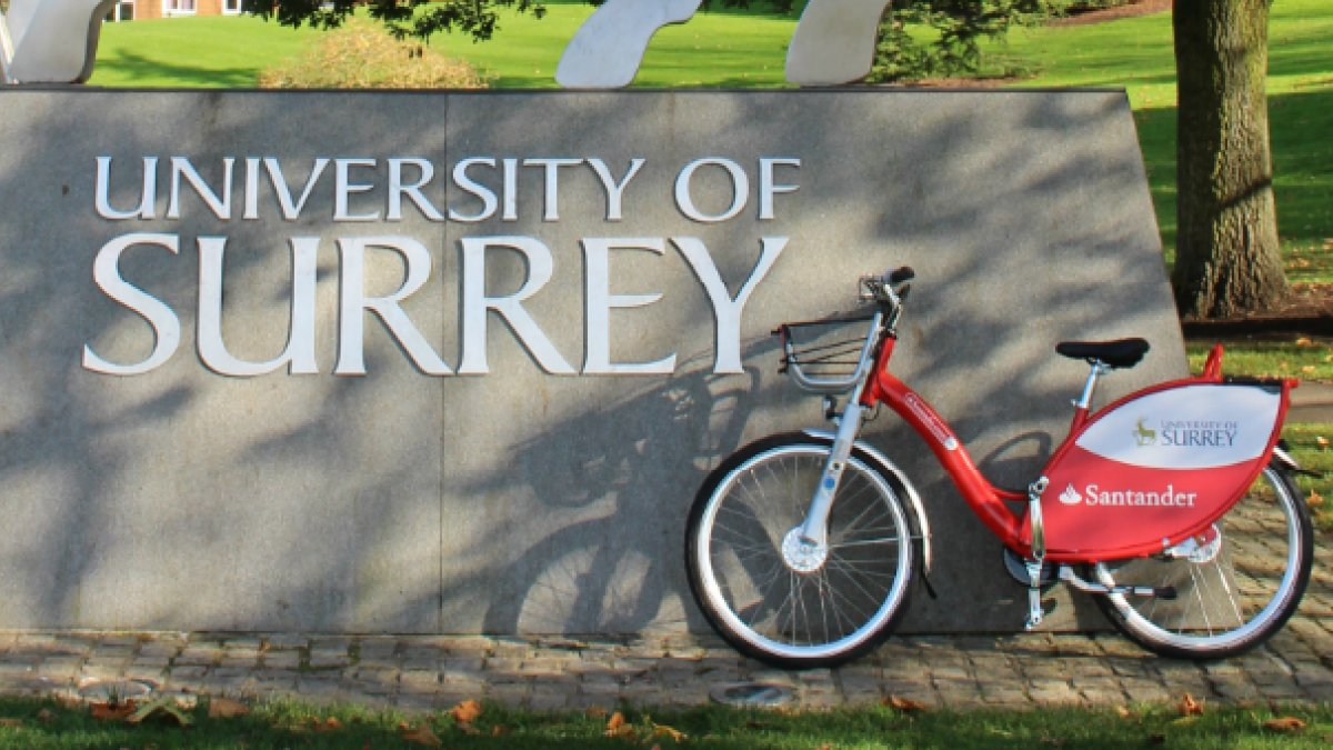 Bike resting about University of Surrey sign