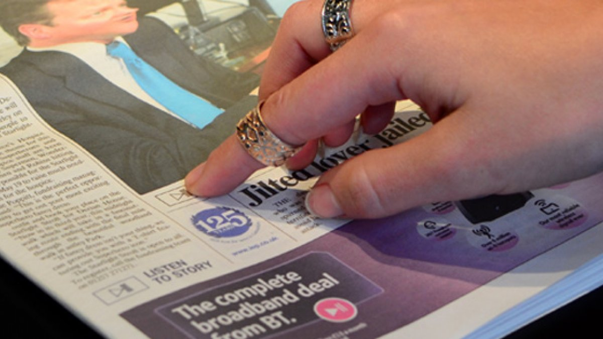 Finger pointing at newspaper