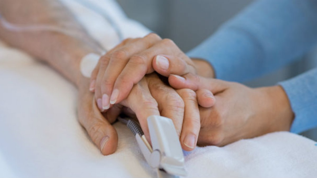 Two hands holding in hospital