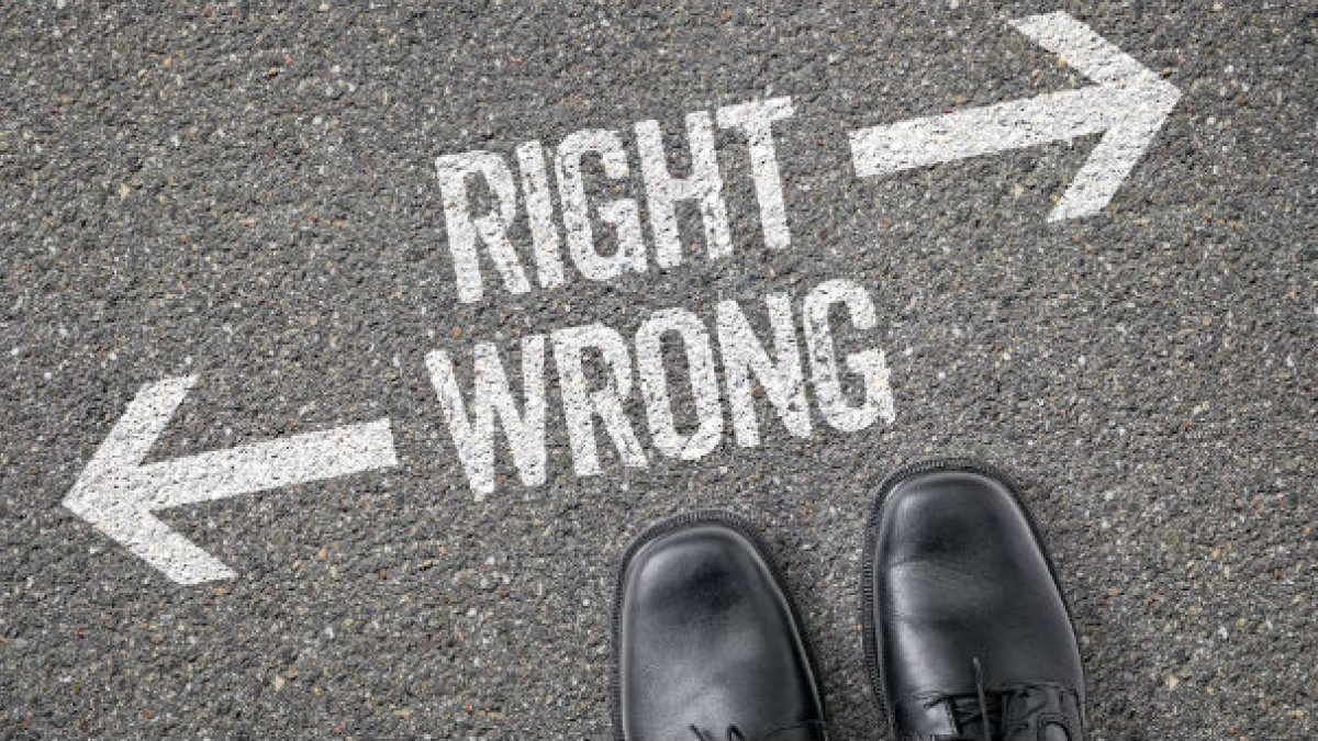 "Two feet standing over writing saying ""RIGHT"" and ""WRONG"" on the ground"