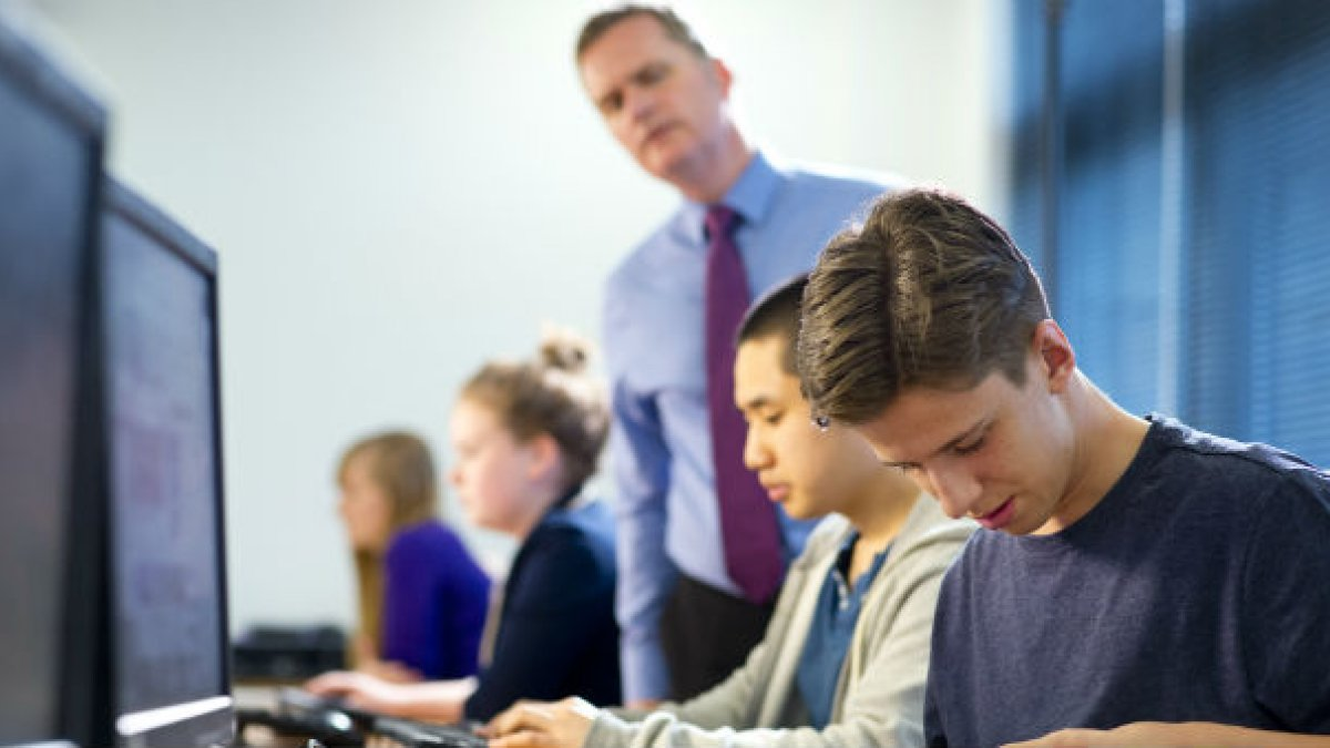 Students and teacher working in front of computers