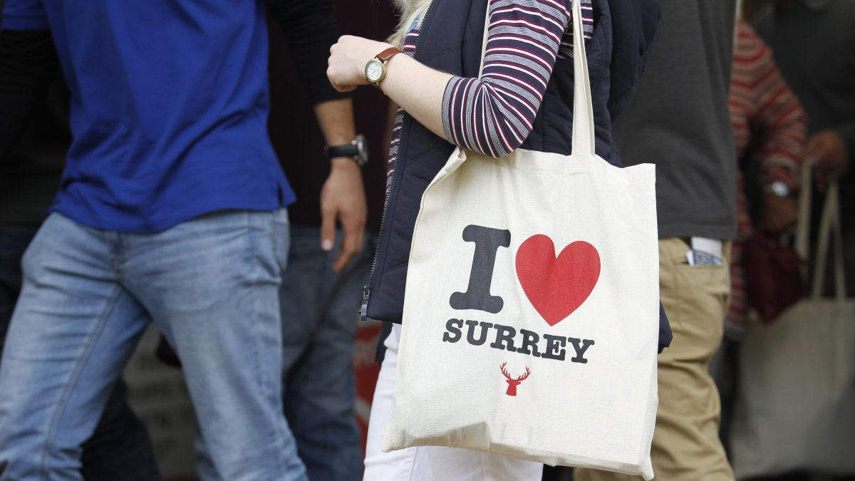 Person holding an 'I love Surrey' bag in a crowd