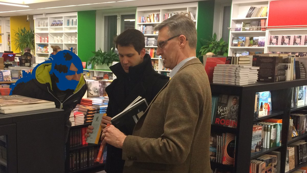 Three men standing in bookshop
