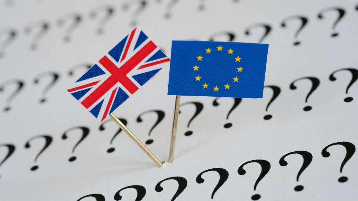 British and European flags sit on a page of question marks