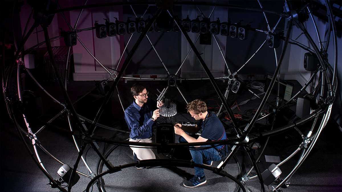 Two men adjusting the sound sphere facility equipment
