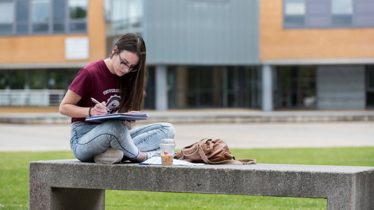 Student sitting on bench reading