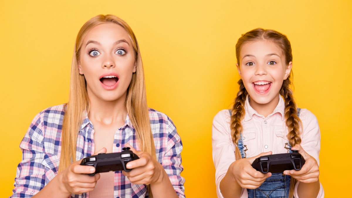 A young girl and an older girl playing computer games sat next to eachother
