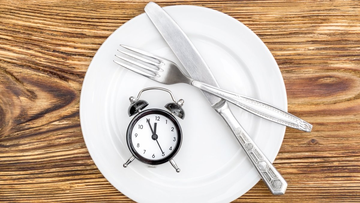 Knife and fork on plate next to alarm clock