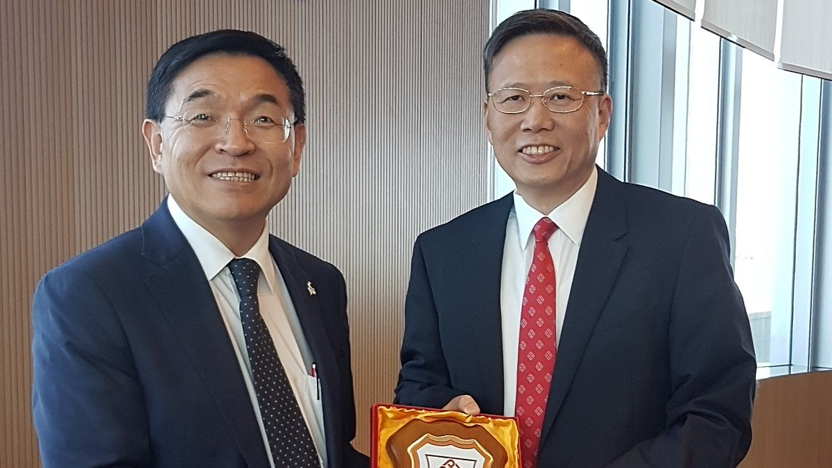 Professor Jin-Guang Teng, President of PolyU (right) presents a souvenir of PolyU's School of Hotel and Tourism Management to  Professor G.Q. Max Lu, President and Vice-Chancellor of the University of Surrey