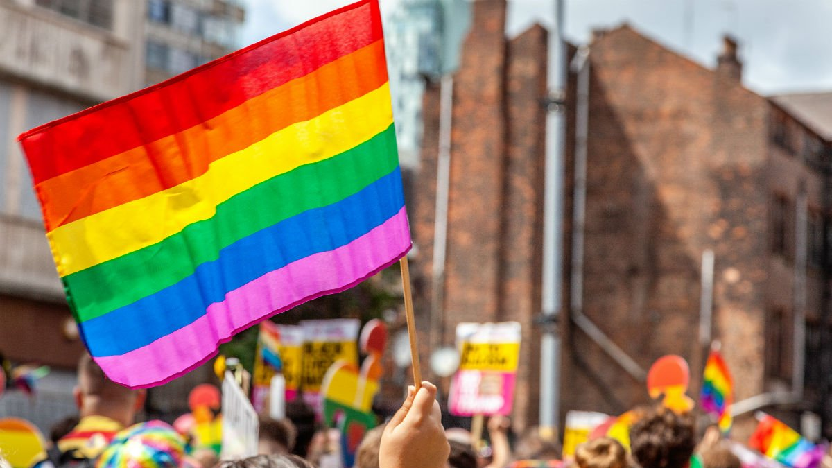 An LGBTIQ flag is waved in a crowd of people
