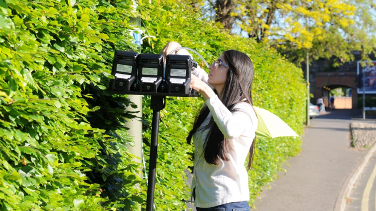 Woman measuring air quality at Stoke Road