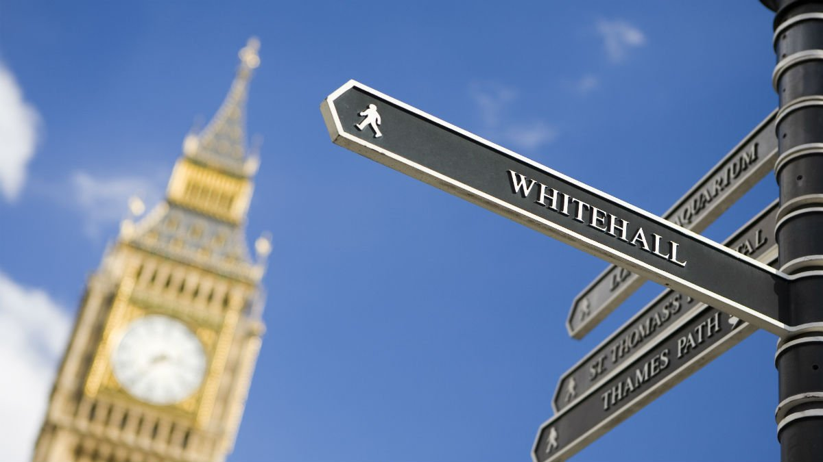 A tourist sign pointing towards Whitehall with Big Ben in the background
