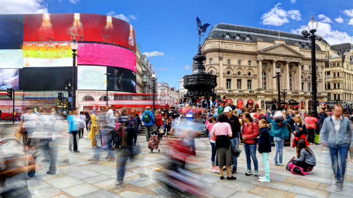 Lots of tourists walk around Piccadilly Circus in London
