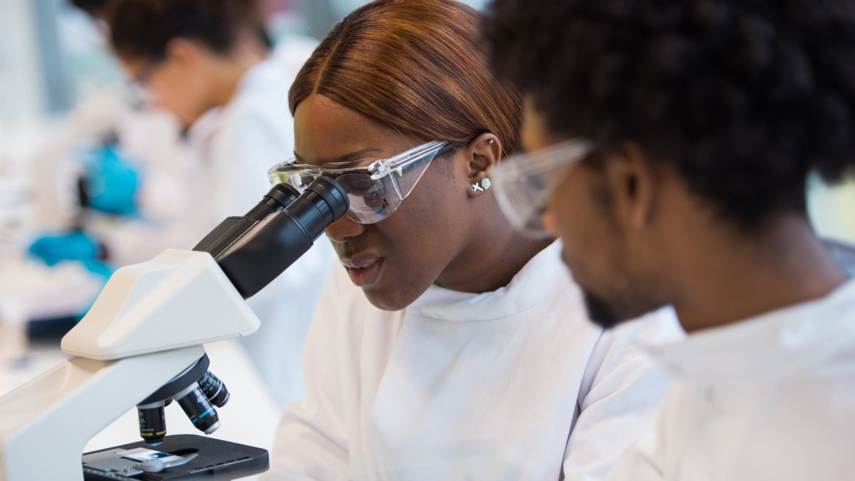 Female student looking through microscope