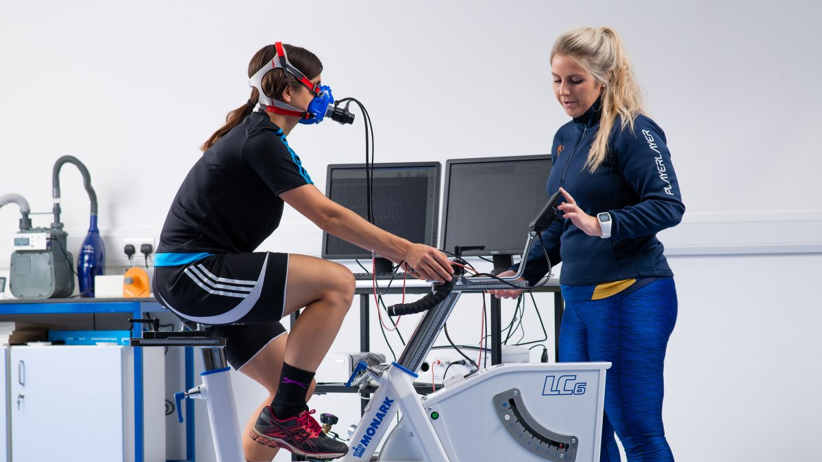 Participant cycling on exercise bike whilst staff member monitors their breathing