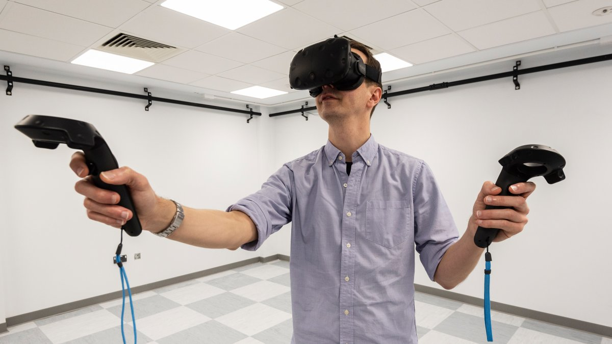 Man wearing a virtual reality headset and holding virtual reality controllers