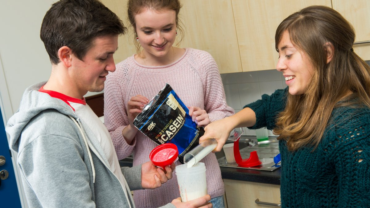 Students pouring casein into a beaker