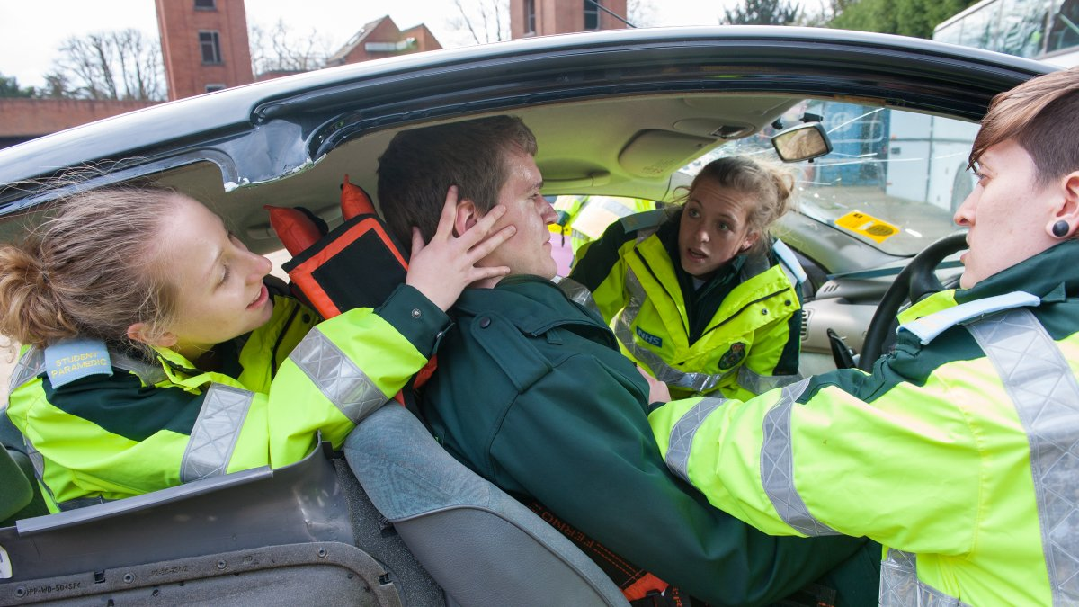 Paramedic students treating male in a car