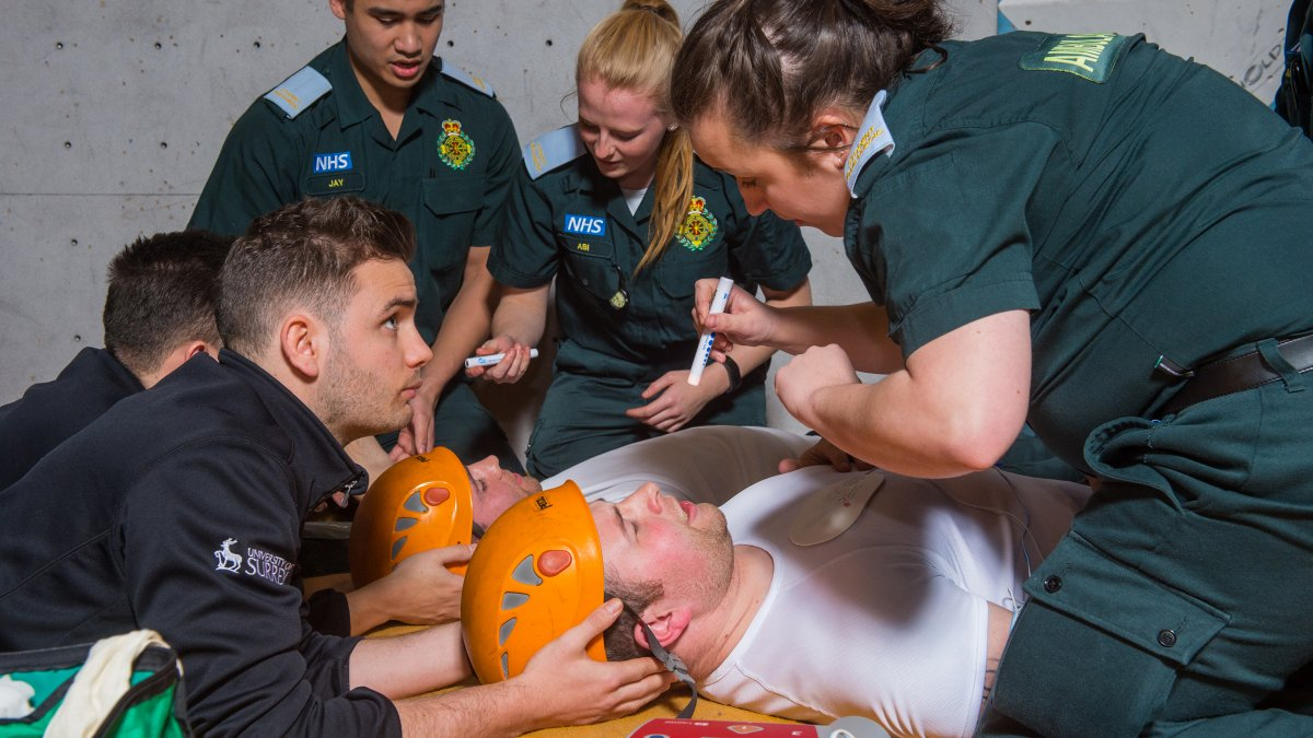 Paramedic student treating climber while another person holds their head