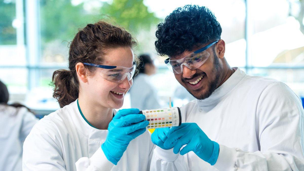 Two students holding a tub of litmus paper with pH scale on the side