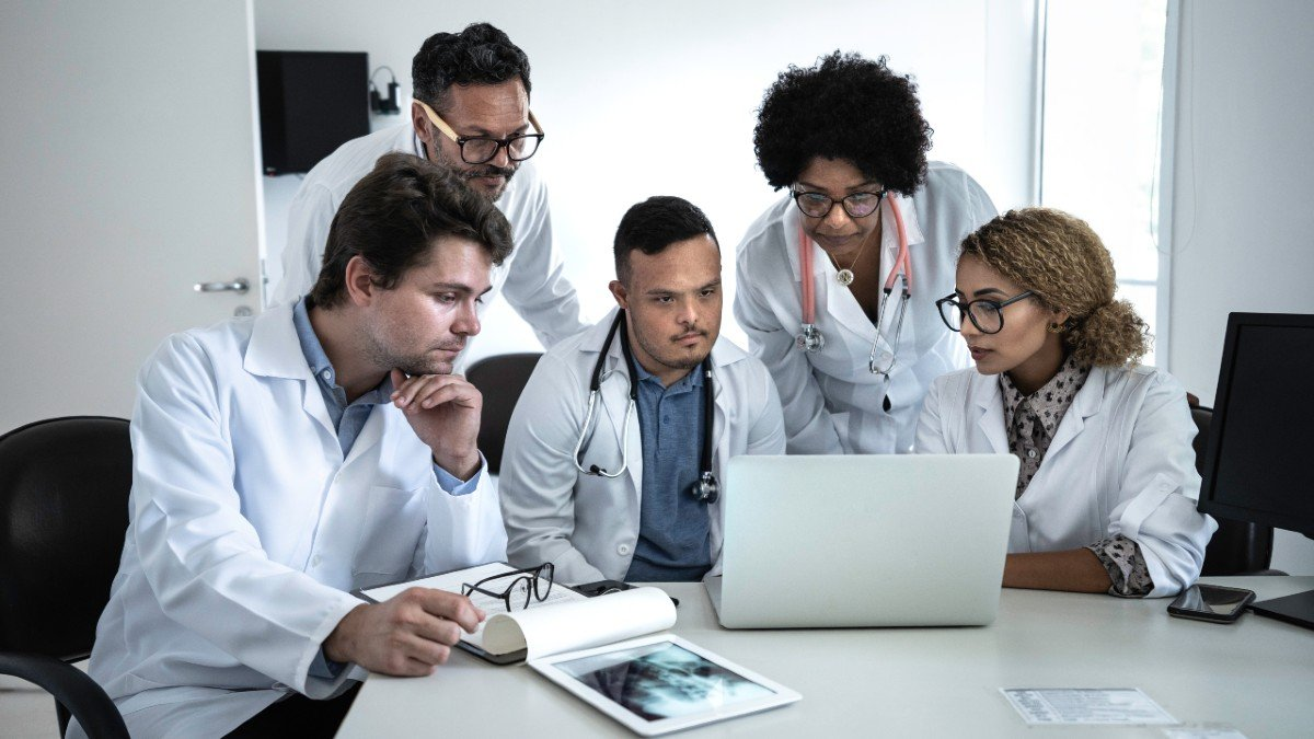 Group of doctors gathered around a laptop