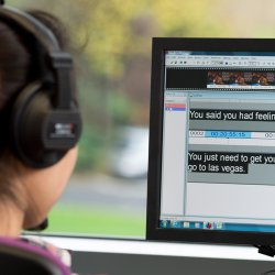 Student using translation software on computer screen whilst wearing headphones